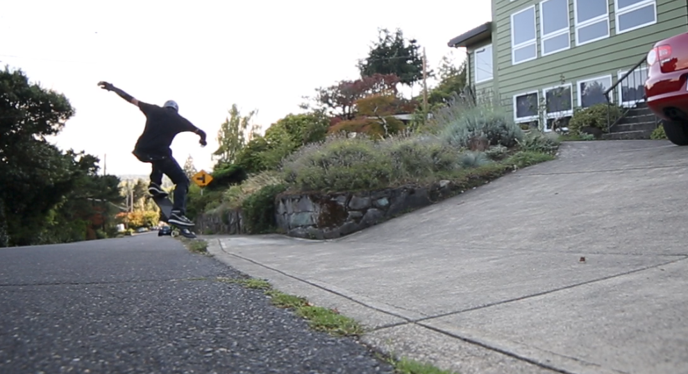 Transition the back foot onto the tail and ollie off the driveway curb back into the street.
