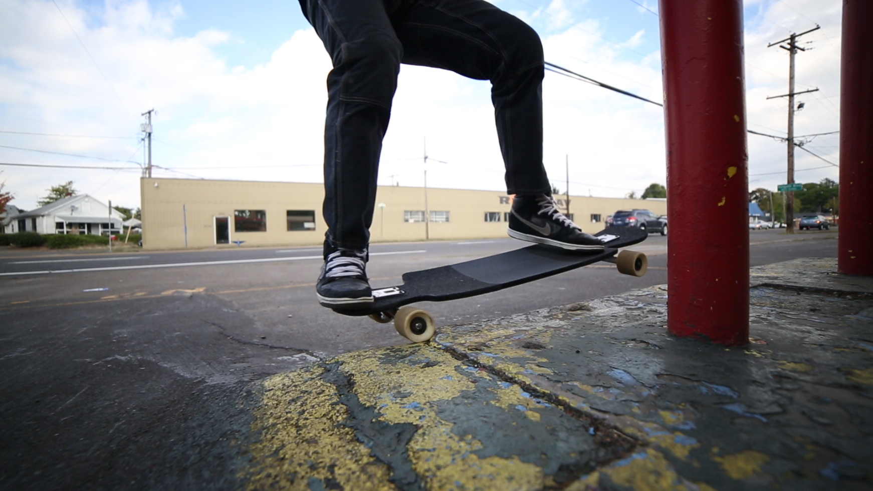 Riding up onto a curb and grinding frontside.